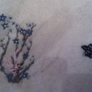 The flowers are my friend's blossom backpiece and the black blob represents a cartoon cat that she is now having removed from her lower back. The doll